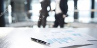 stock-photo-focus-on-documents-and-pen-on-the-table-blurred-people-on-background-256784239